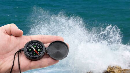 hand with compass on background of sea