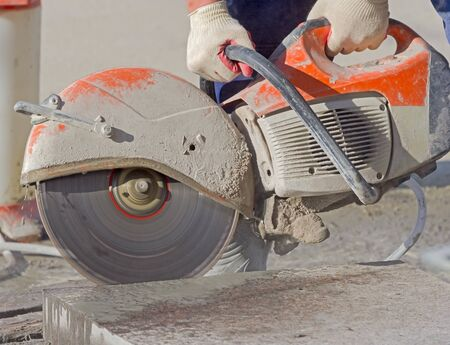 Construction worker operated Circular saw with a diamond blade for cutting asphalt and concrete