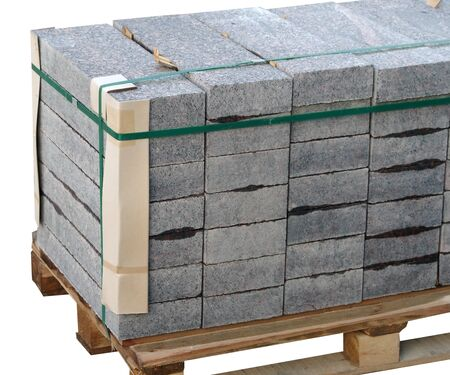 The pallet with a stack of concrete curbstone on white background Фото со стока