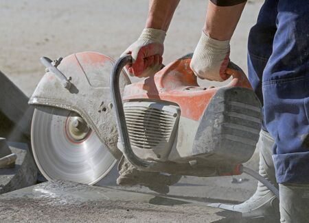 Construction worker operated Circular saw with a diamond blade for cutting asphalt and concrete Фото со стока