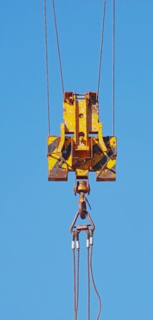 Crane hook hanging on steel ropes isolated on background blue sky