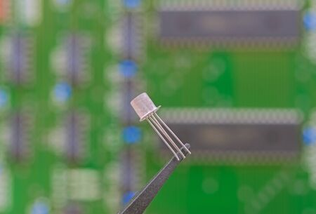 Electronic component held with tweezers over a green motherboard