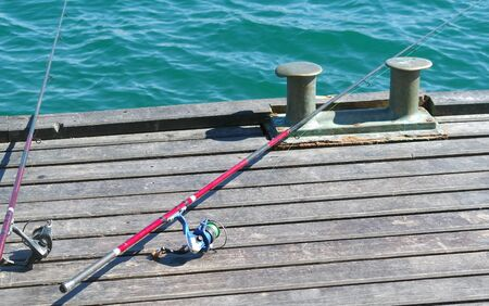 Two fishing rods on the pier ready for fishing Фото со стока