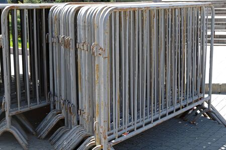 Many old movable metal fences stacked on public square Фото со стока