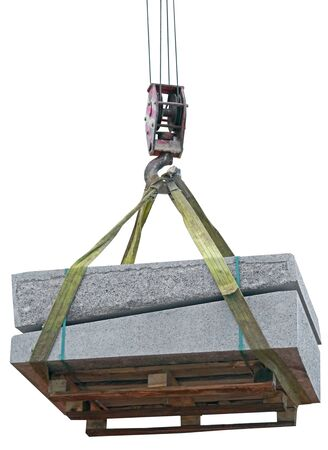 a crane lifts pallet with a stack of concrete curbstone on white background