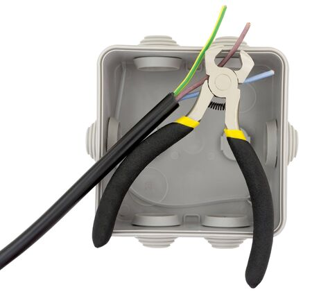 Electrician is cutting copper wiring with cutting pliers during installing electrical box