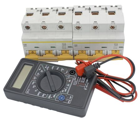 Electrical circuit breaker and digital multimeter on white background