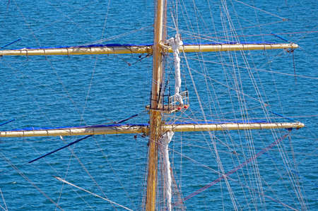 Masts and rigging of a sailing ship against blue sea
