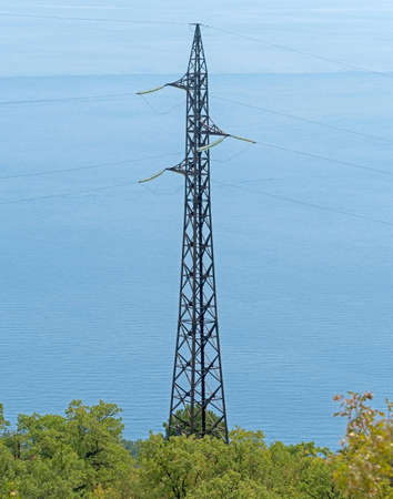 electric tower high voltage post with blue sea