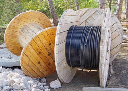 black wire electric cable with wooden coil of electric cable on construction sites