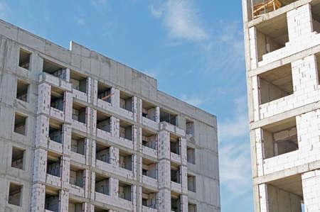 High-rise building under construction against blue sky