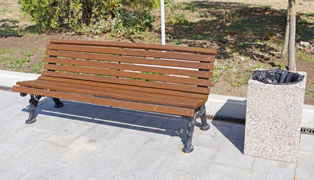 Park Bench and garbage container in the city park Фото со стока