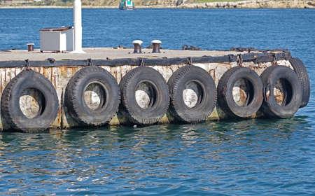 car tire with a metal chain on a old concrete sea pier Фото со стока