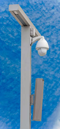 IP security camera and led Street lantern mounted on post against the blue sky