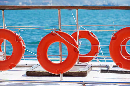 Orange lifebuoy attached to board the ship