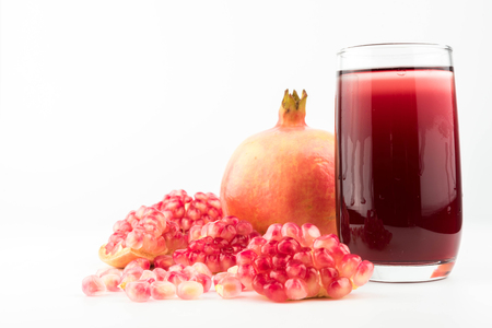 Glass of pomegranate juice with fruit isolated on white. Stock Photo