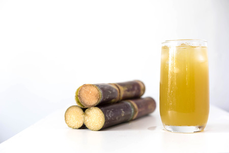 cooking oil: Fresh sugar cane juice in glass on table white background Stock Photo