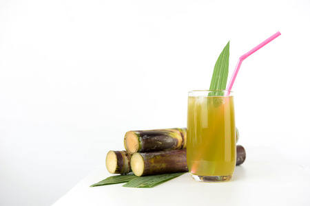 molasses: Fresh sugar cane juice in glass on table white background Stock Photo