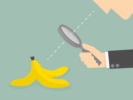 Businessman looking to a banana peel through a magnifying glass