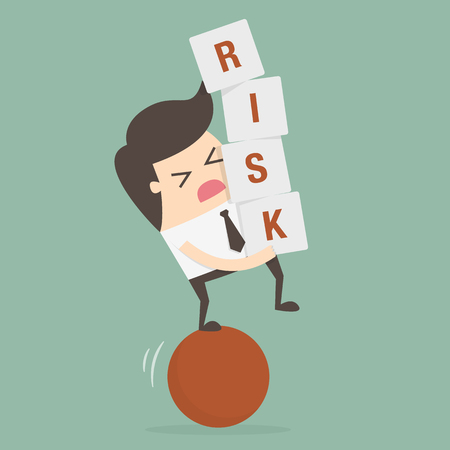 Businessman stepping on a ball while carrying risk blocks