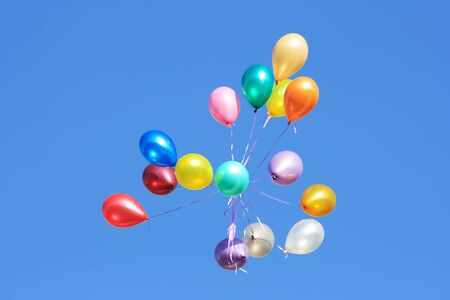 descriptive: Flying balloon after celebration in the clear blue sky Stock Photo