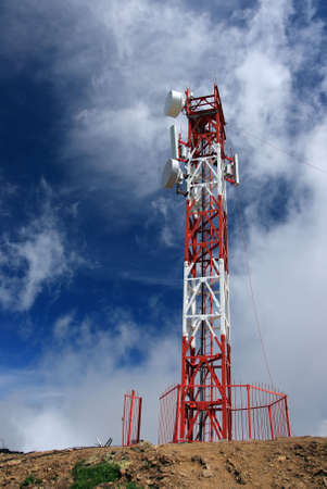 New cellular antenna in the mountains. Clouds and blue sky are on the background.