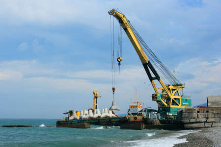 Maritime crane load in the barge by concrete breakwaters