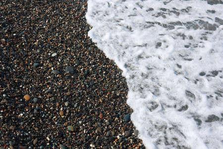Sea coastline. Pebbles and water.