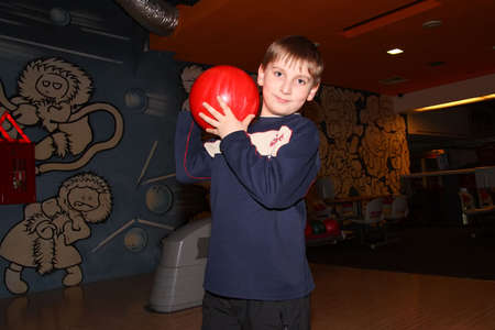 School boy with red bowling ball