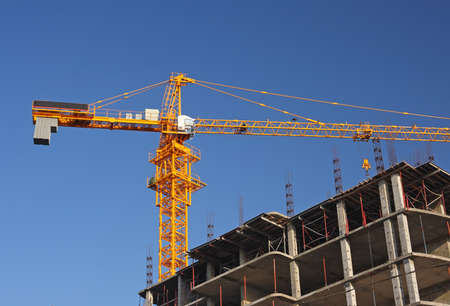 Yellow construction crane in midday