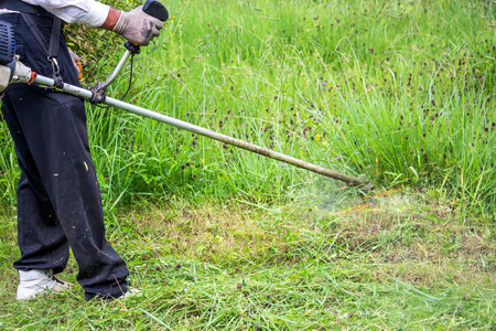 grass cutting: The gardener cutting grass by lawn mower. Stock Photo