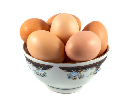 ellipse: brown chicken eggs in a cup isolated on white.