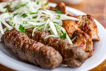 Traditional Georgian mtsvadi pork barbecue and Kebab with onion and parsley. Stock Photo