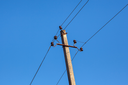 Mast electrical power line against blue sky.