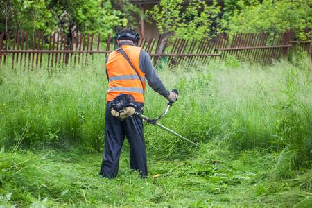 잔디 깎는 기계로 잔디를 자르는 정원사.