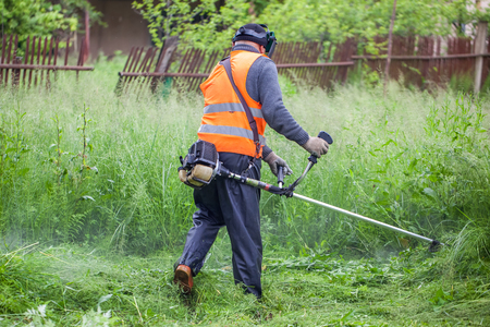 cutter: The gardener cutting grass by lawn mower. Stock Photo