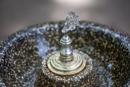 wash: Close up water drops flowing from fountain.