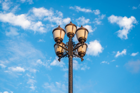 The old retro lamp post and the beautiful white and blue sky.