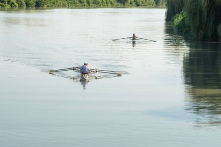 Teenage sportsmen in a boat, rowing on the river Rioni, Poti, Georgia. Stock Photo