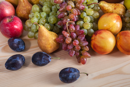 autumnal fruit still life on rustic wooden table background.