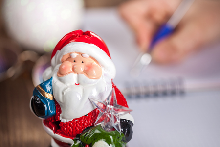 Hands with a pen, notebook and an envelop for letter. A girl is ready to write a letter to Santa Claus. dreams come true, magic holidays and merry Christmas, gifts time
