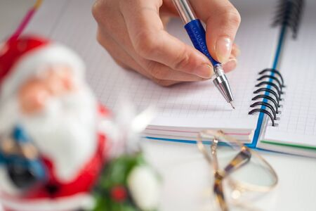 Hands with a pen, notebook and an envelop for letter. A girl is ready to write a letter to Santa Claus. dreams true, magic holidays and merry Christmas, gifts time Stock Photo
