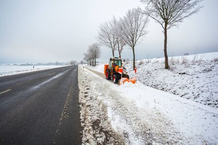 tractor cleans the bicycle road from snow, winter landscape. Stock Photo