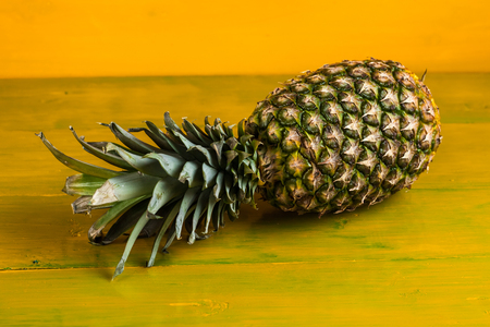 Ripe pineapple on a yellow wooden background.