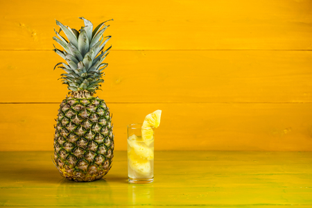 Ripe pineapple and juice in a glass on a yellow wooden background.