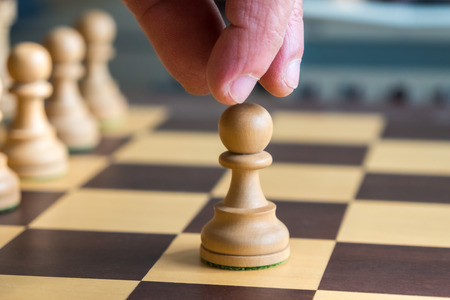 Hand moving a white pawn on a chess board.
