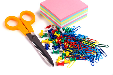 Scissor, tacks, papers and paper clips on white background.