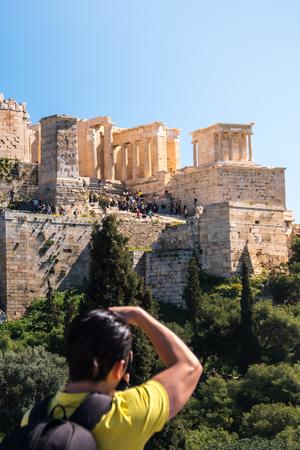tourist takes photos Acropolis, Parthenon, Athens, Greece.