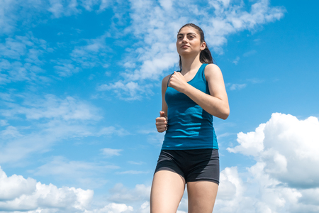 Young sports girl runs on a background of blue sky.