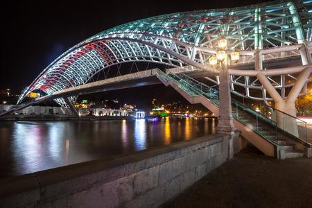Pedestrian bridge of peace over the Mtkvari (Kura) River in Tbilisi at night. Georgian flag.